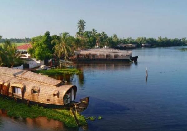 a-houseboat-parked-on-the-shores-of-ashtamudi-lake-in-kerala,-india-cpxg9w